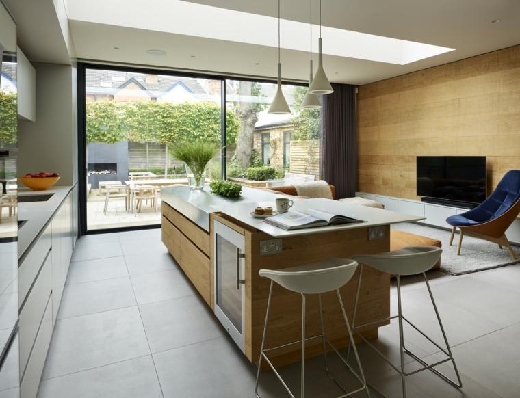 Isola con frigo, cucina con isola centrale, soggiorno con parete di legno, pavimento piastrelle grigie