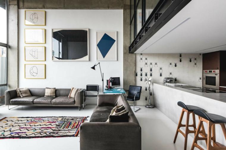 Soggiorno con divani grigi, cucina con isola centrale, soluzioni per dividere soggiorno e cucina