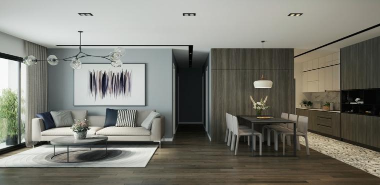 Divano di colore beige, cucina con mobili di legno, soggiorno con pavimento parquet