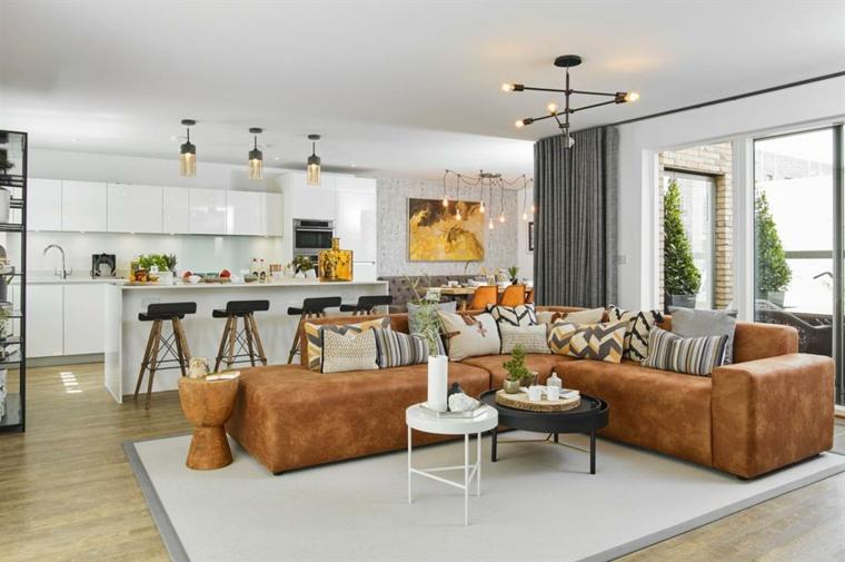 Divano pelle marrone, tavolini di metallo rotondi, cucina con isola, pavimento in parquet