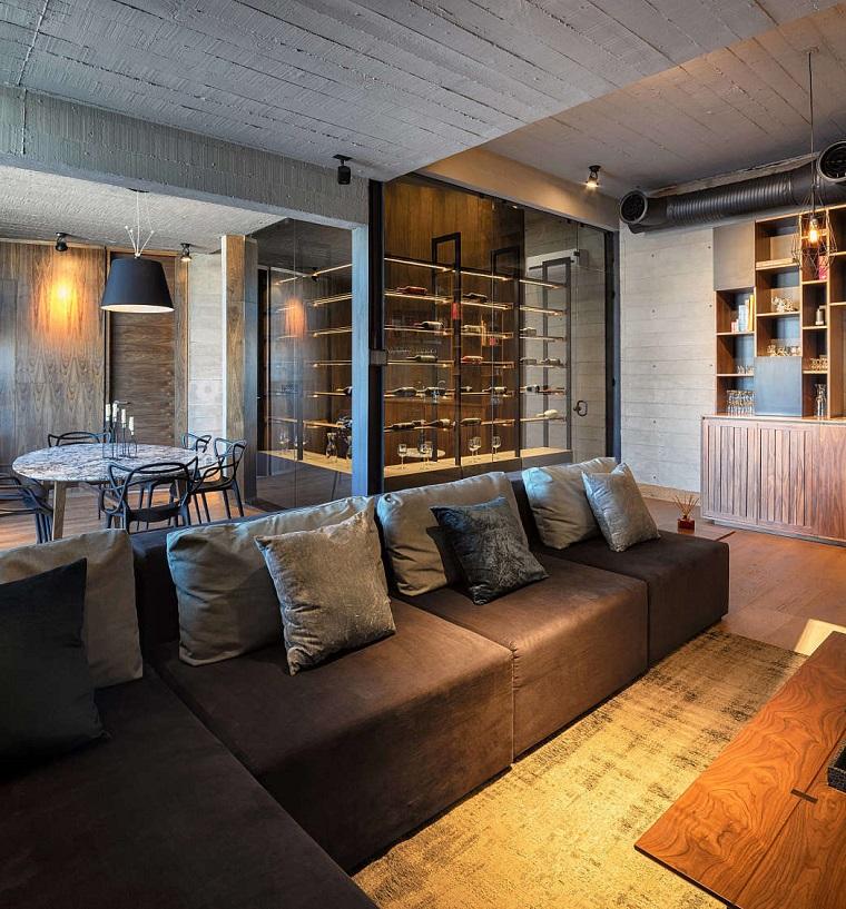 Divano di colore marrone, tavolo da pranzo rotondo, cantina per il vino, soffitto con travi di legno