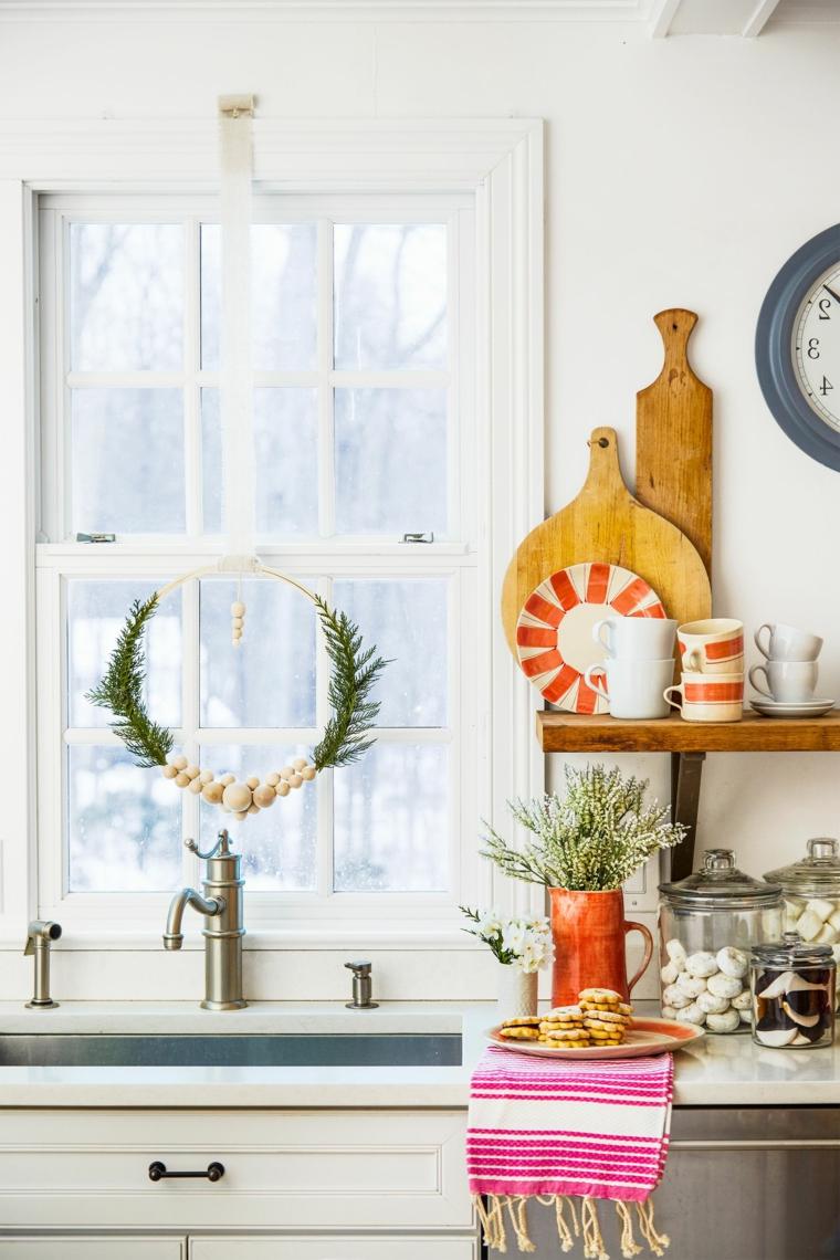 finestra con festone di rametti verdi cucina con decorazioni di natale