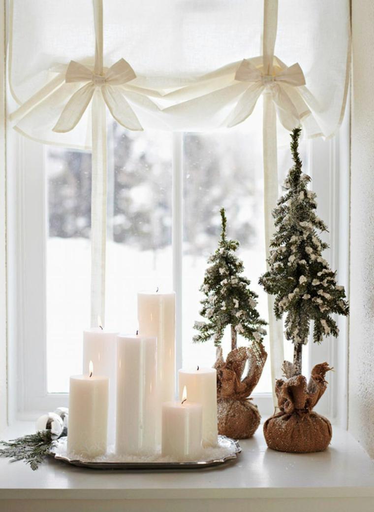 finestra decorata con candele e alberelli di natale tende bianche legati con fiocchi
