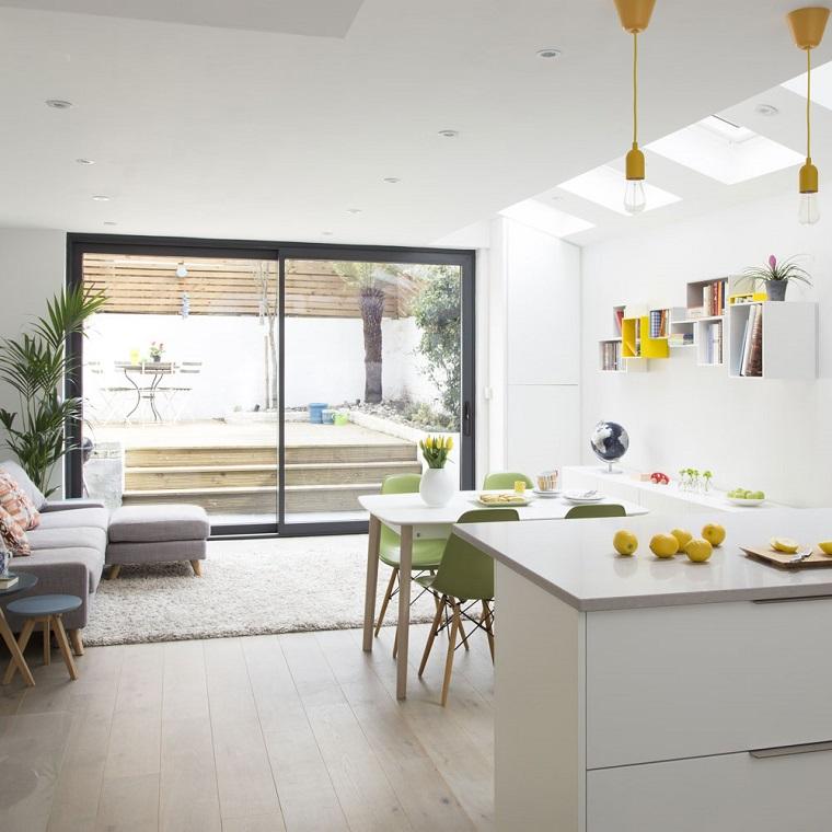 Open space con cucina, divano angolare grigio, tavolo da pranzo e sedie, lampadari sospesi