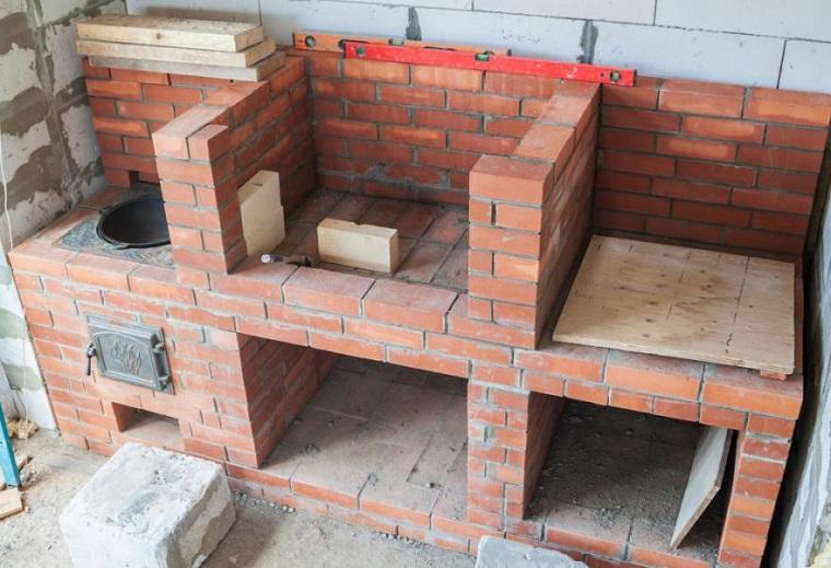 Montaggio barbecue con mattoni rossi, spazio per griglia e piano di lavoro