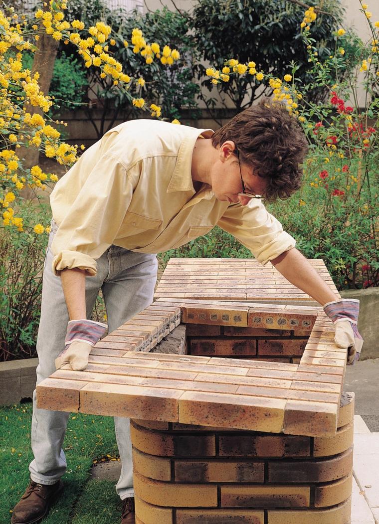 Uomo che monta un barbecue, montaggio di una griglia in muratura