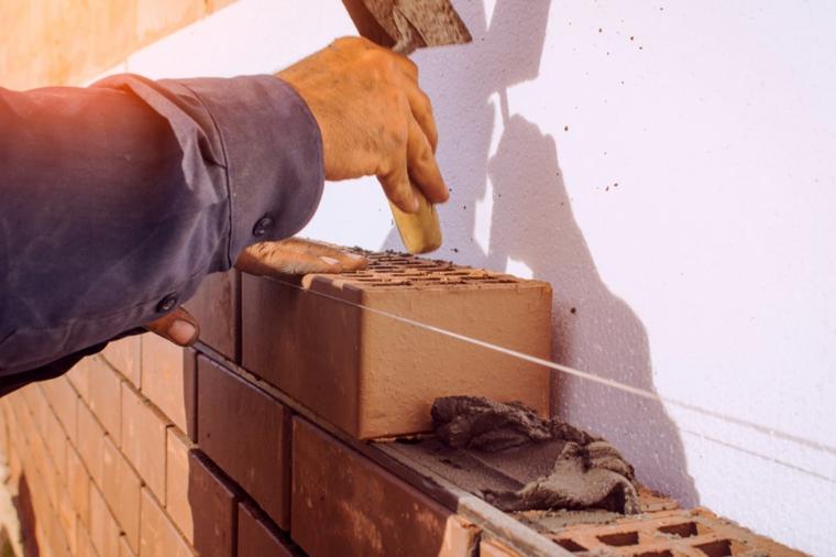 Uomo che posiziona dei mattoni sul muro, costruire barbecue in muratura