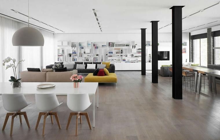 Soggiorno con divani colorati, tavolo da pranzo bianco, pavimento in legno parquet