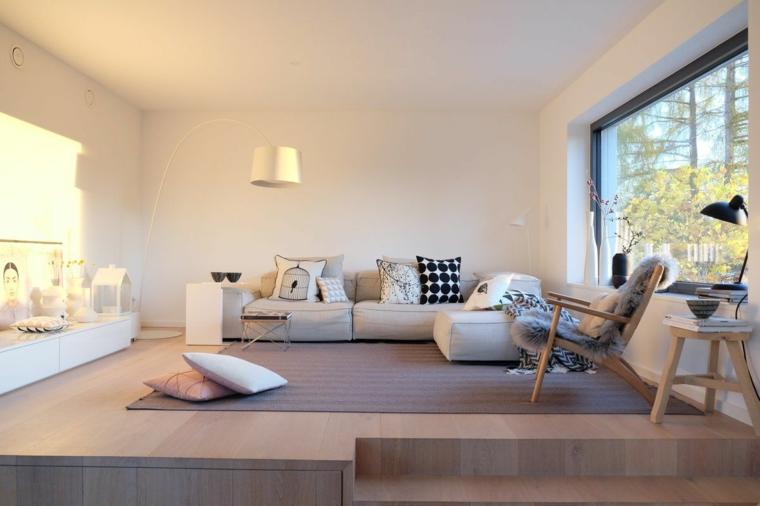 Open floor con soppalco, divano basso in tessuto, mobile bianco basso, tappeto grigio
