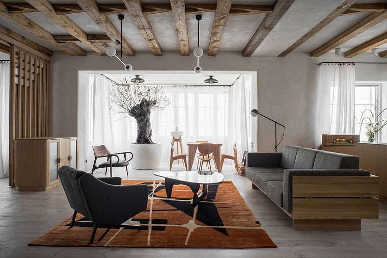 Soggiorno con travi di legno, divano in legno e pelle, loft significato, tappeto con print geometrici