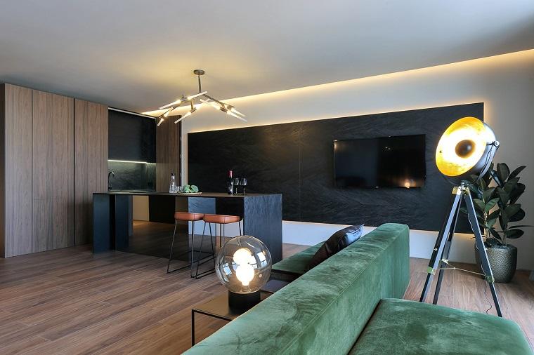 Loft significato, divano di colore verde, isola centrale con sedie, stanza con pavimento parquet