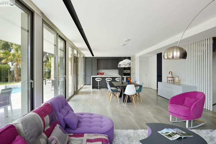 Cucina con isola centrale, divano in tessuto colorato, living con porta finestra, casa con piscina