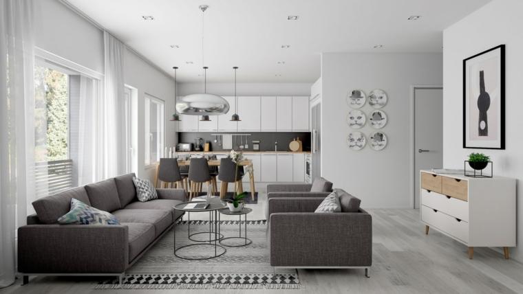 Divano di colore grigio, tappeto grigio, cucina con mobili bianchi, tavola da pranzo in legno