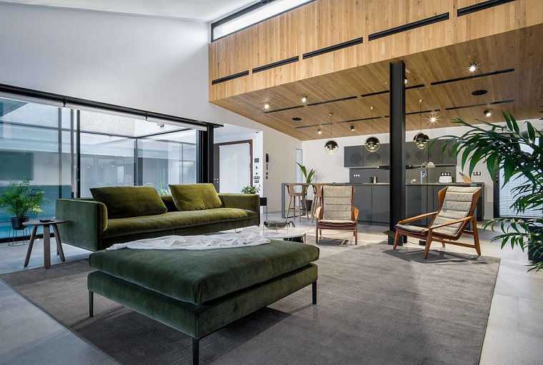 Arredare salotto e sala da pranzo insieme, divano di colore verde, cucina con mobili scuri