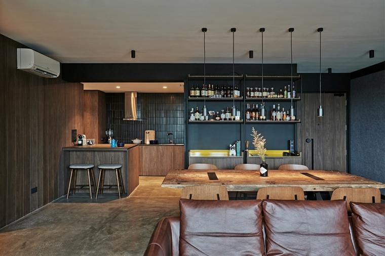 Cucina con isola, tavola da pranzo in legno, divano in pelle, lampade a sospensione