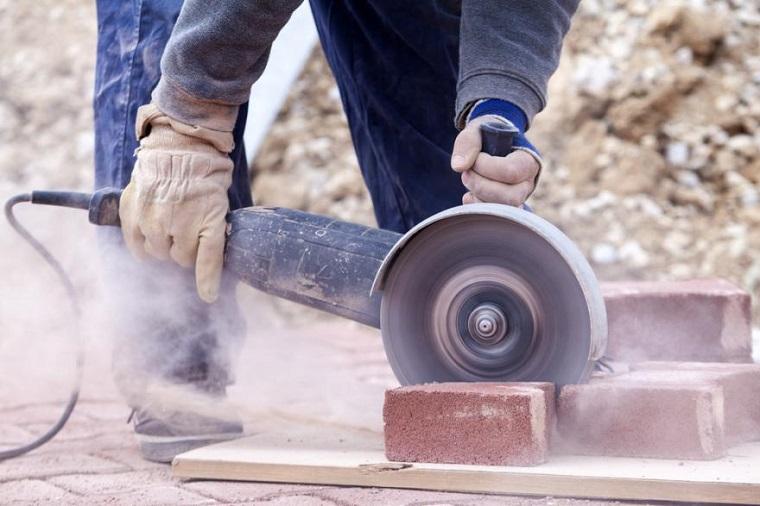 Uomo che taglia pezzi di mattoni, modelli di barbecue in muratura