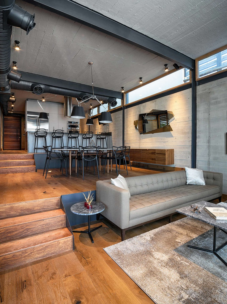 Loft con soppalco, divano in pelle grigio, pavimento in legno con scalini, tavolino in marmo