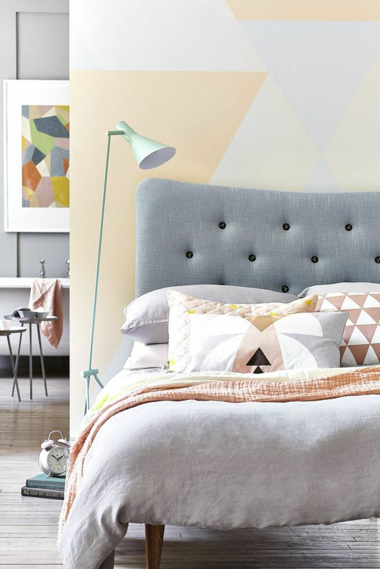 testata letto grigia tessuto cuscini lampada terra stanza da letto piccola