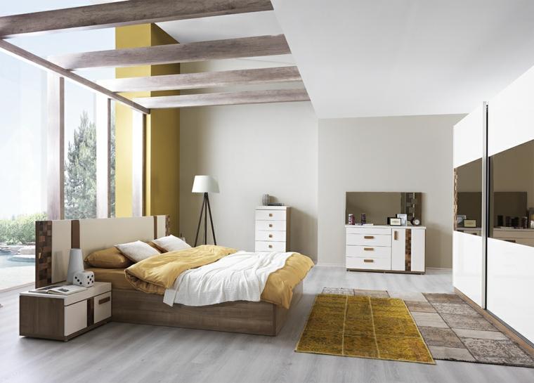 Soffitto con travi in legno, armadio con porte specchi, letto in legno, tappeti colorati