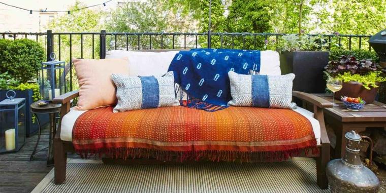 Divano con cuscini e coperte, arredare balcone piccolo e stretto, ringhiera in ferro battuto