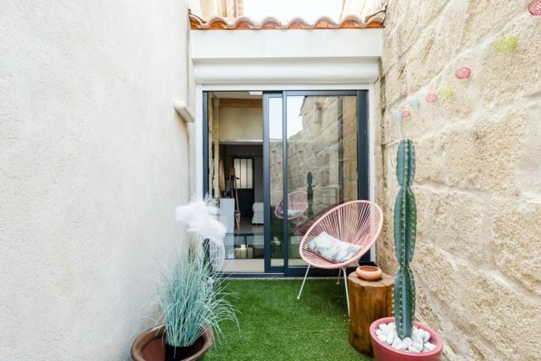 Arredare balcone piccolo e stretto, mobili in legno, pavimentazione erba finta e piante tropicali