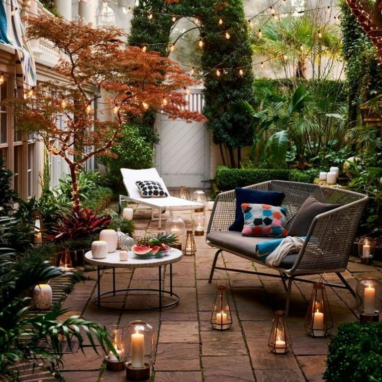Arredare terrazzo low cost, arredo con divano in rattan e tavolino, lanterne con candele sul pavimento