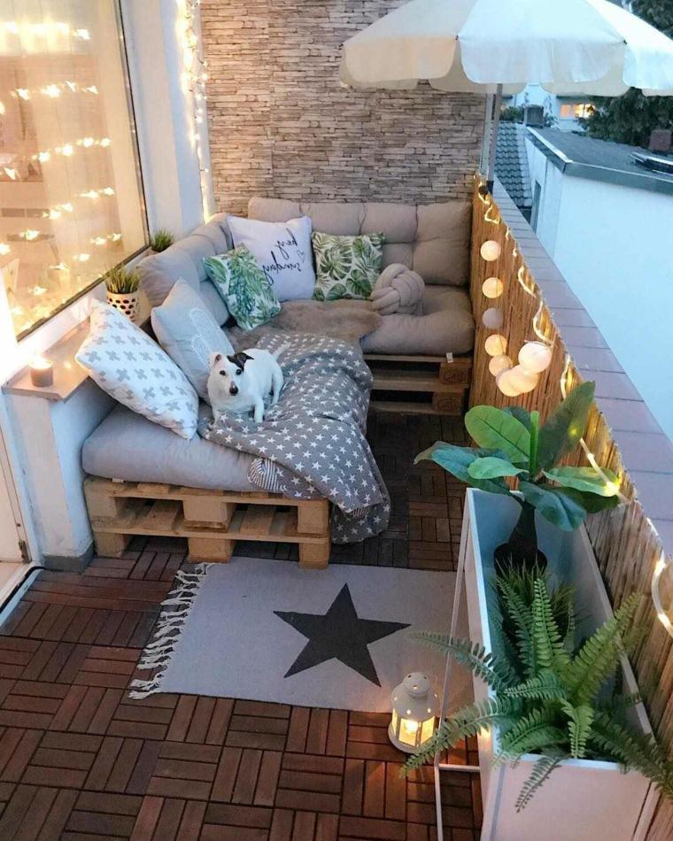 Arredare terrazzo low cost, balcone con divano in pallet e cuscini, piccolo tappeto sul pavimento del terrazzo