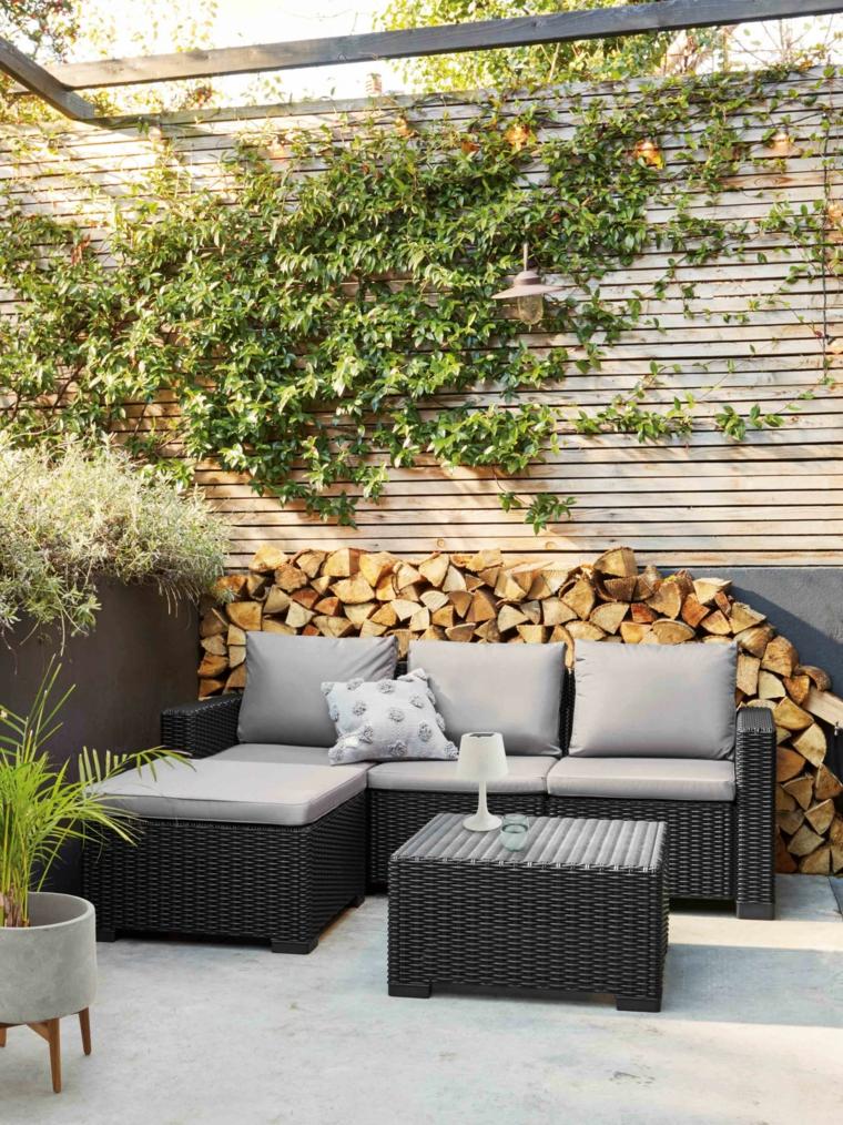Terrazzo con divano in rattan e tavolino, come arredare un terrazzo, ringhiera in legno e piante rampicanti