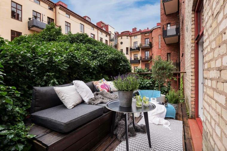 Arredare terrazzo appartamento, panchina di legno con cuscinera, vaso su un tavolino