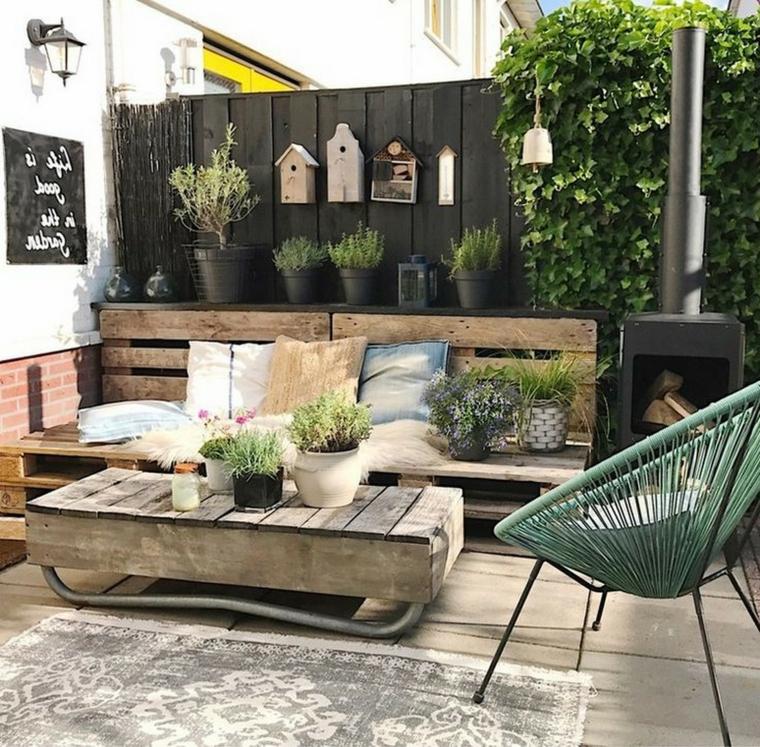 Arredare terrazzo appartamento, divano in pallet con cuscini, tavolo in pallet con vasi di piante