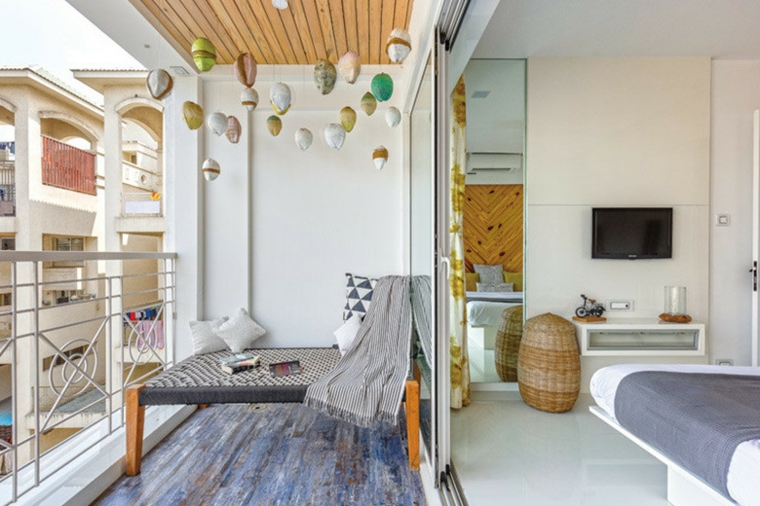 Balcone con ringhiera di ferro battuto, tavolino e sedia, arredare terrazzo low cost