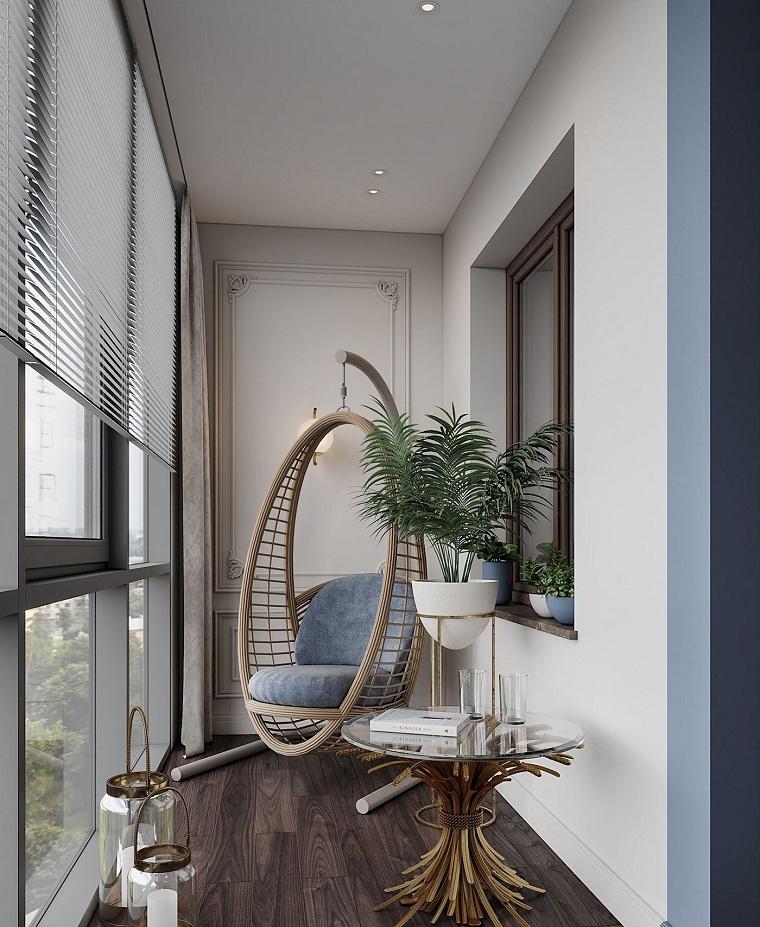 come arredare un piccolo terrazzo coperto poltrona dondolo decorazione con vaso pianta dalla foglia verde arredo con tavolino di vetro
