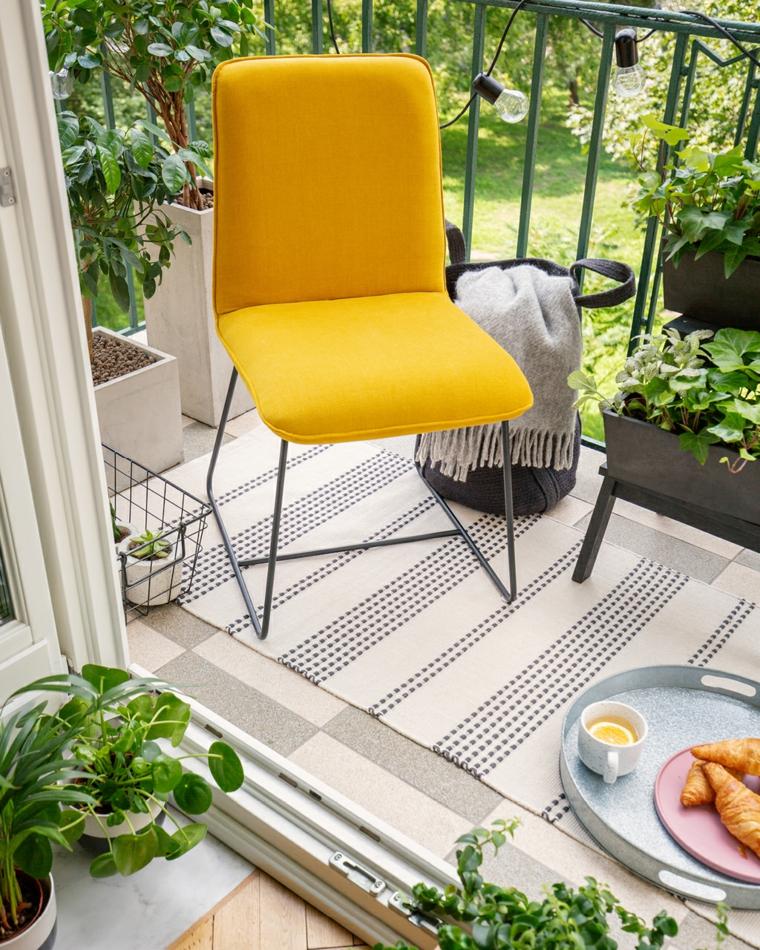 Arredare balcone stretto e lungo, arredo con una sedia gialla, balcone con ringhiera in ferro battuto