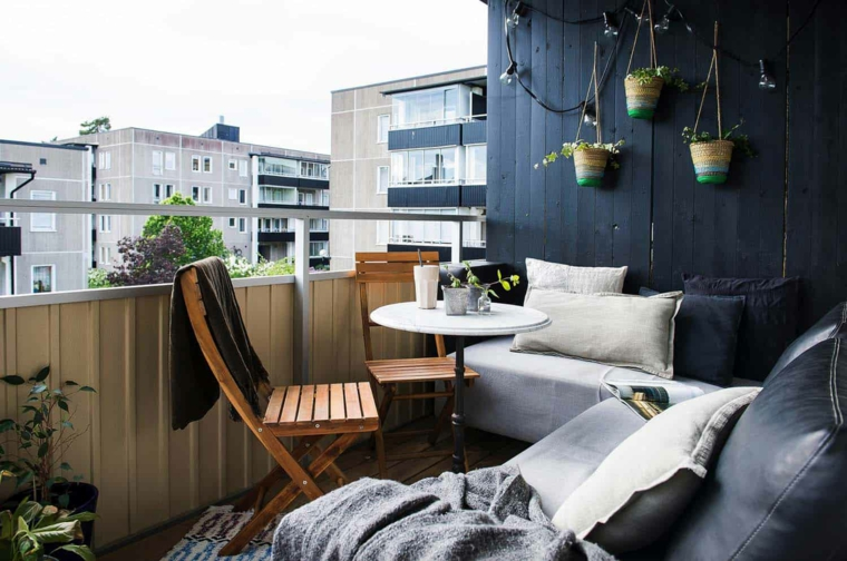 Arredare terrazzo appartamento, parete in legno con vasi sospesi, set di mobili divano e tavolino