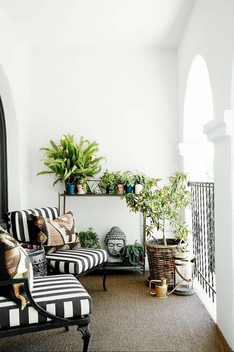 Terrazzo con ringhiera in ferro battuto, due sedie con cuscini, arredare balcone stretto e lungo