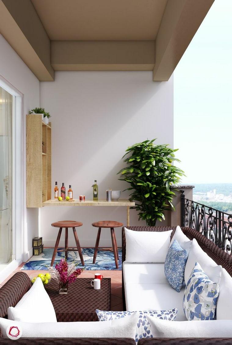 Arredare terrazzo appartamento, terrazzo con ringhiera in ferro battuto, zona bar con due sgabelli di legno
