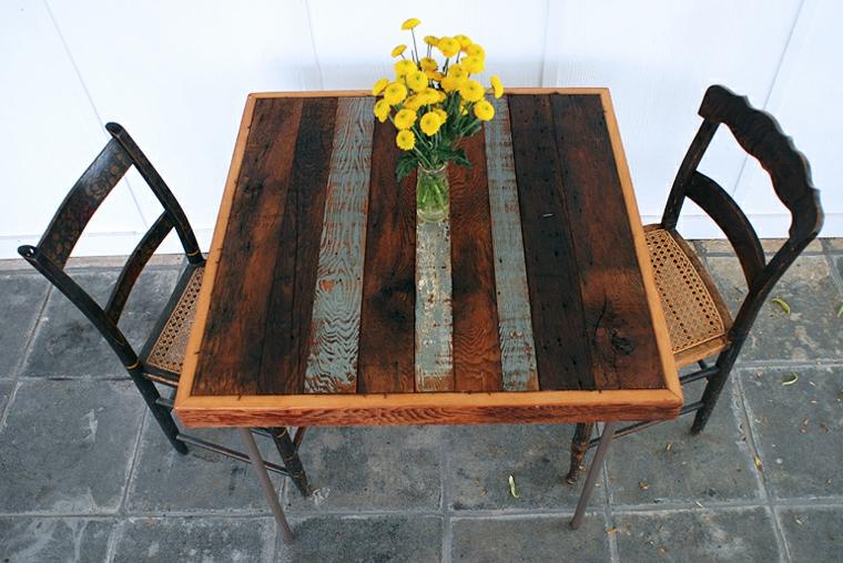 Tavolo con bancali, tavolino da giardino con un vaso di fiori e due sedie