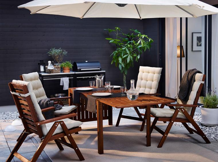 come sistemare le lanterne in casa balcone con set di mobili in legno e ombrellone zona barbecue