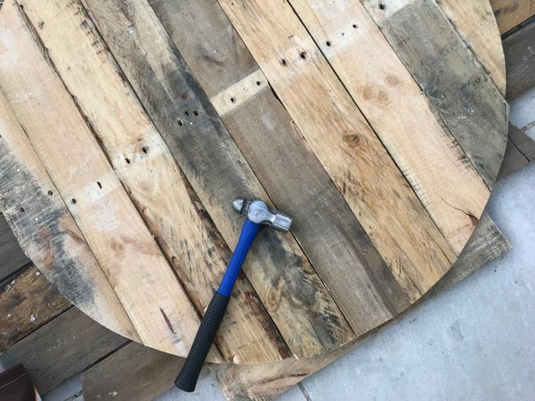 Tavolo con bancali, tavolo rotondo di pallet con un martello posizionato sopra