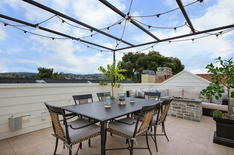 Arredo terrazza con tavolo da pranzo e sedie, pergola con fili di lucine