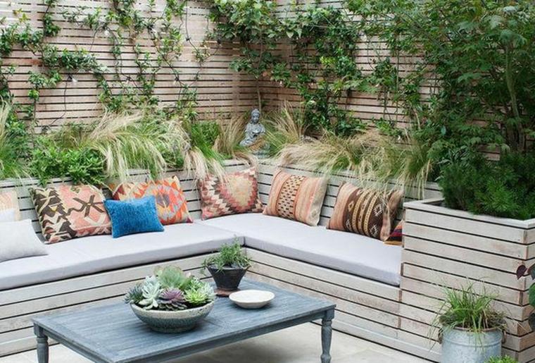 Terrazza con ringhiera in legno, dicano in pallet con cuscini, tavolino con vasi di piante grassi