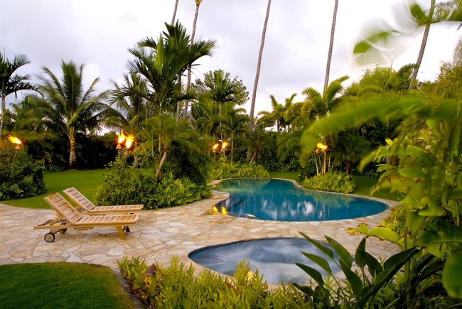 giardino tropicale circondato palme piscina lettini prendisole