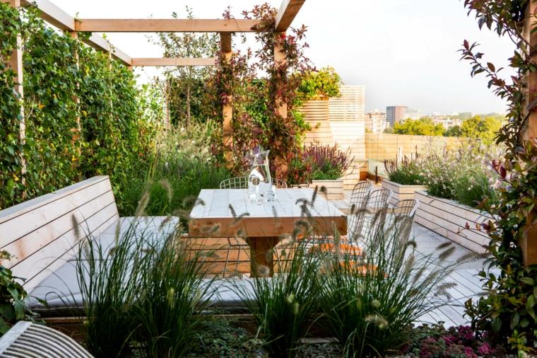 Terrazzo con pergola di legno, parete con piante dalla foglia verde, arredo con mobili in pallet