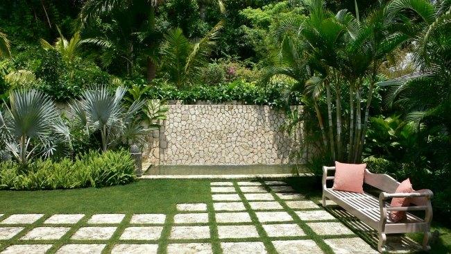 progettare giardino palme svariate muri pietra panchina legno