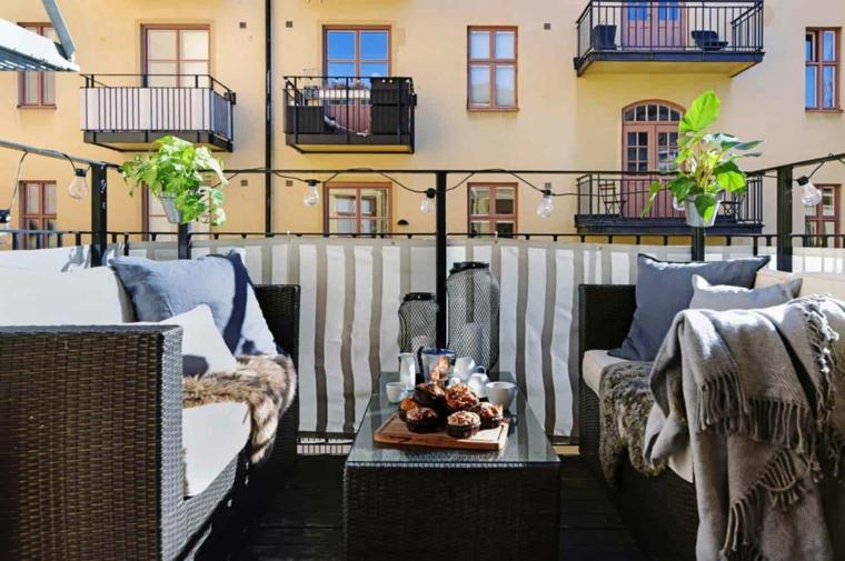 Come abbellire un terrazzo, arredo con divano e tavolino in rattan, terrazzo con ringhiera in ferro battuto