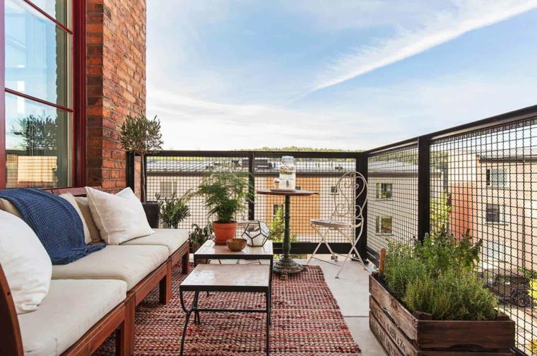 Arredo terrazzo con divano e tavolini, pavimento in piastrelle e tappeto, balcone con ringhiera a rete