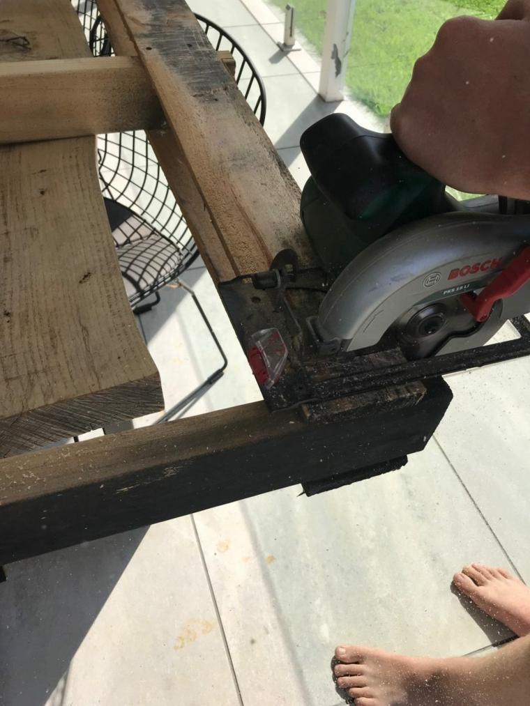 Tavolo con bancali, tutorial di un uomo che taglia il pallet con seghetto elettrico