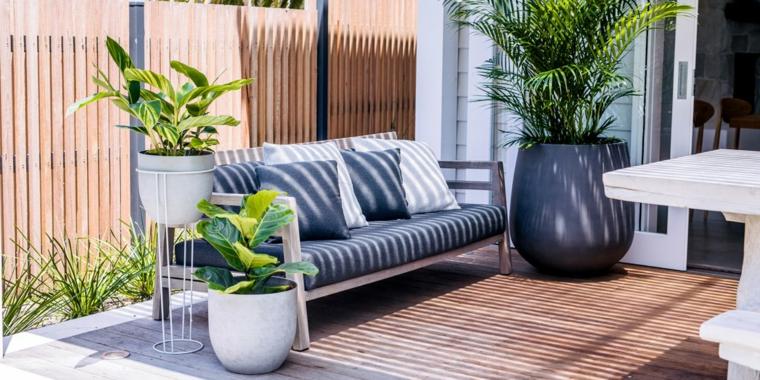Come arredare un terrazzo, ringhiera terrazzo in ferro battuto, divano in legno con cuscineria blu