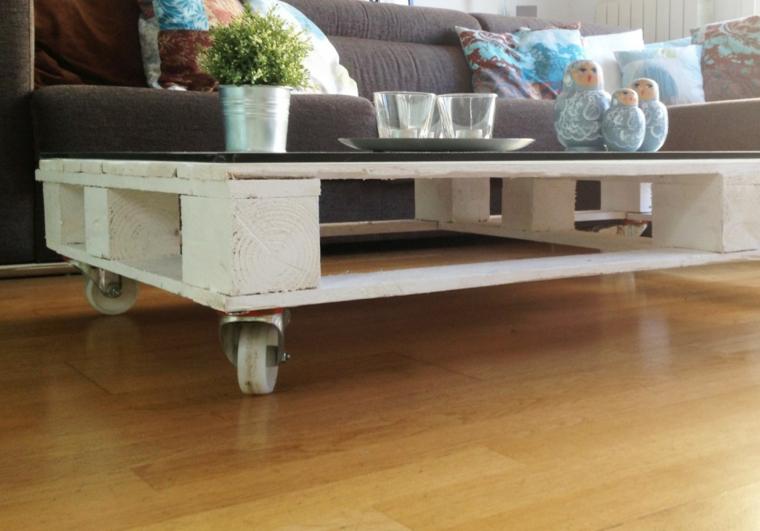 Tavoli fatti con bancali, tavolino da soggiorno con bancale di legno accanto ad un divano