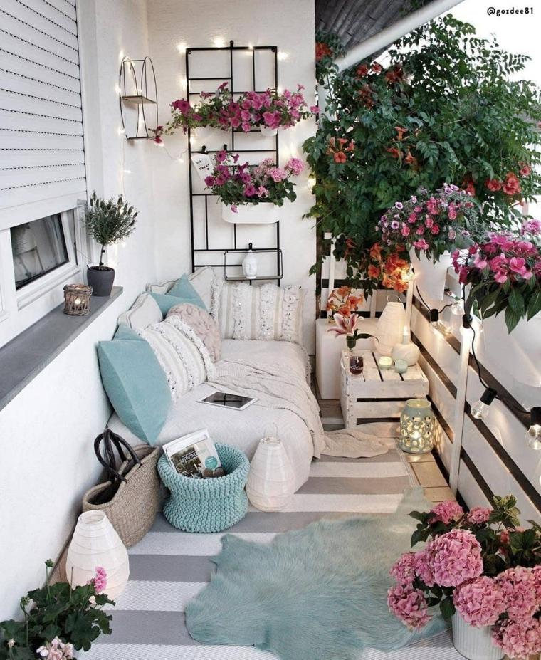 Come arredare un terrazzo spendendo poco, divano in pallet con cuscini, ringhiera in legno con fili di lampadine